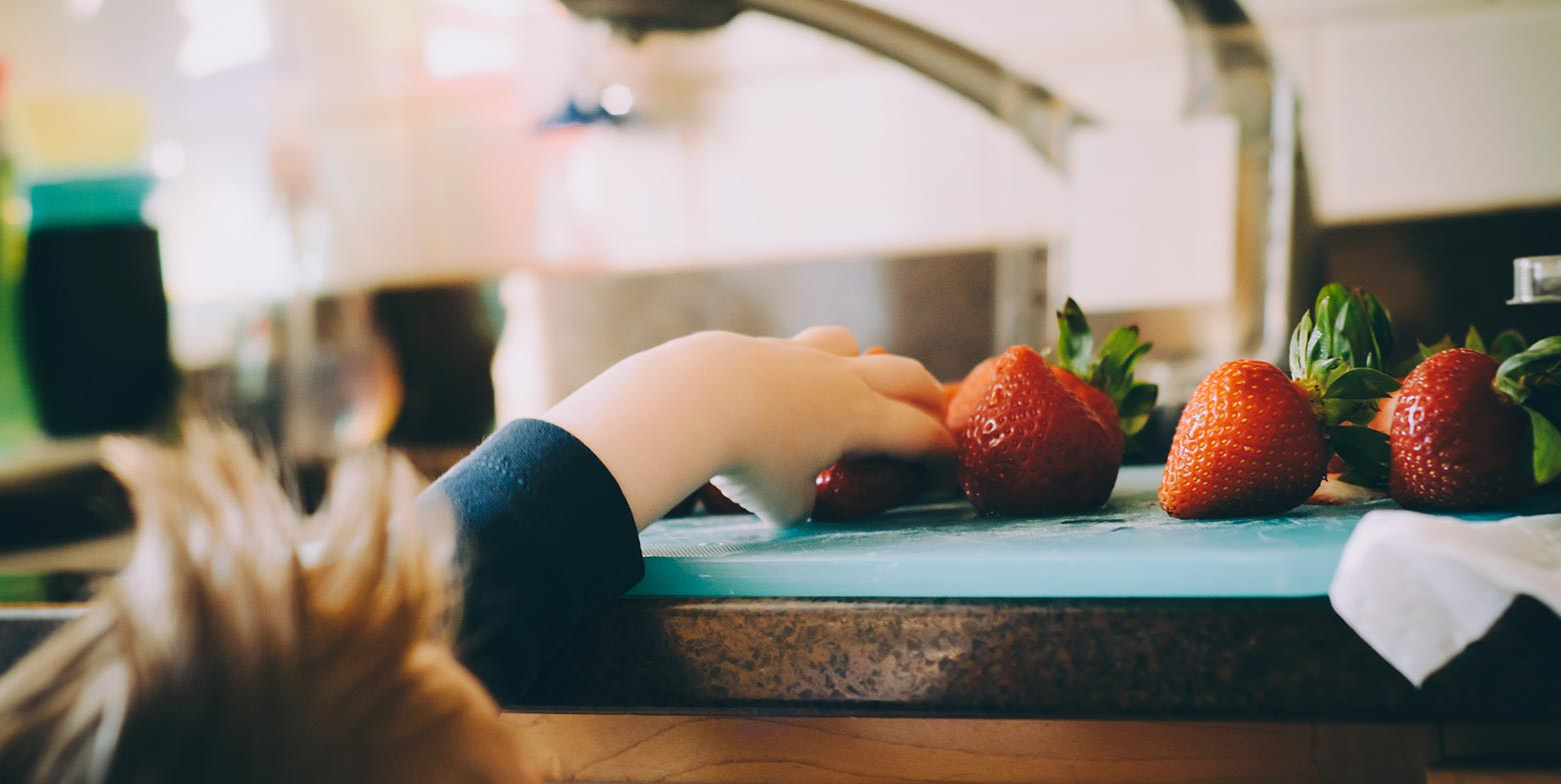 Niño cogiendo fresas de la mesa